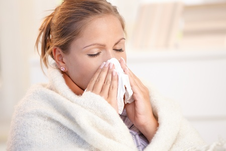 Young woman having flu, feeling bad, blowing her nose, wrapped up in blanket. Stock Photo - 8895481