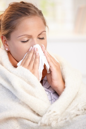 hanky: Young woman having flu, feeling bad, blowing her nose, wrapped up in blanket.