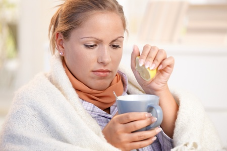 tea cosy: Young female caught cold, feeling bad, wrapped up in blanket, squeezing lemon to her tea.