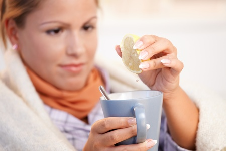 tea cosy: Young woman having flu, feeling bad, wrapped up in blanket, squeezing lemon to her tea.