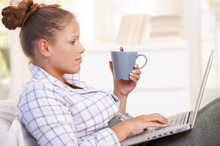 nighty: Young female working at home in bed, using laptop, drinking tea, coffee. Stock Photo