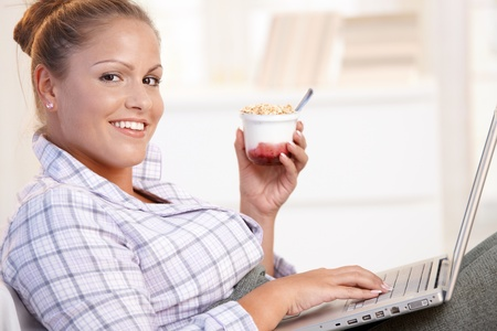 Pretty girl browsing Internet in bed, using laptop, smiling, eating yoghurt. Stock Photo - 8895498