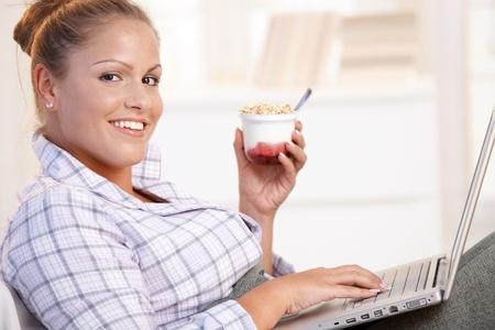 Pretty girl browsing Internet in bed, using laptop, smiling, eating yoghurt. Stock Photo - 8895498