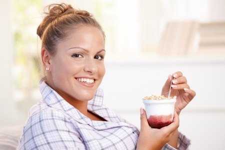 Attractive young woman dieting, eating yoghurt at home. Stock Photo - 8895487