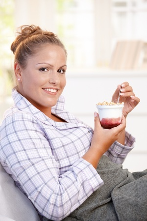 Attractive young woman dieting, eating yoghurt in bed at home. Stock Photo - 8908744