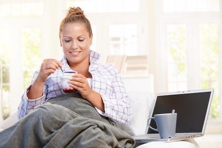 Young female having breakfast at home, dieting, eating yoghurt in bed, using laptop. Stock Photo - 8895485