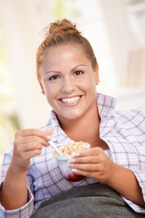 Young female having breakfast at home, dieting, eating yoghurt in bed. Stock Photo - 8907192