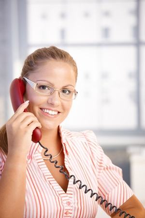 Pretty receptionist working in office, talking on phone, smiling. Stock Photo - 8907191