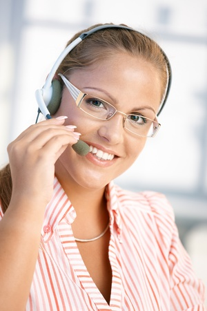 Portrait of pretty dispatcher working in office, using headset, smiling. photo