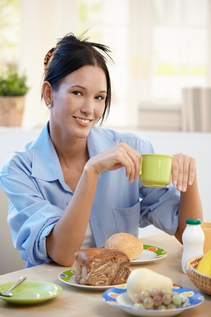 Cheerful young woman having breakfast at home, smiling at camera. photo
