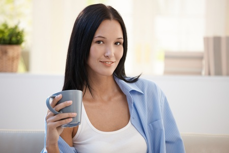 Portrait of young smiling woman holding coffee cup, looking at camera. photo