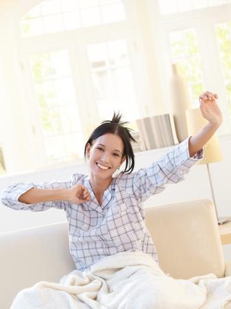 Bonne femme attirante qui s'étend en pyjama sur le canapé dans le salon lumineux, souriant à la caméra.
