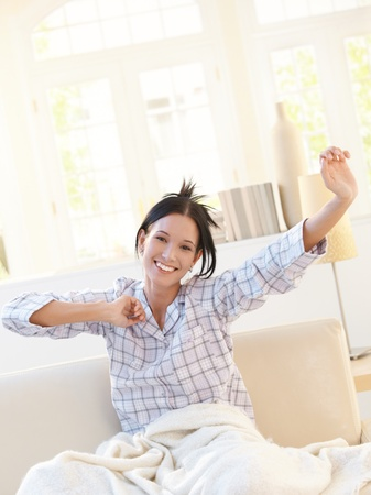 nightdress: Happy attractive woman stretching in pyjama on sofa in bright living room, smiling at camera. Stock Photo