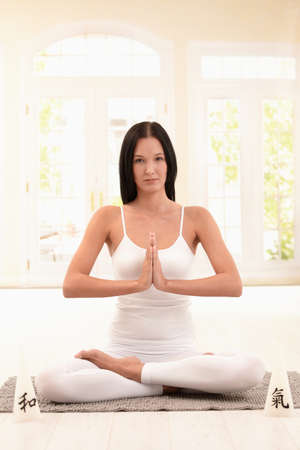 Pretty young woman doing yoga meditation at home, looking at camera. photo