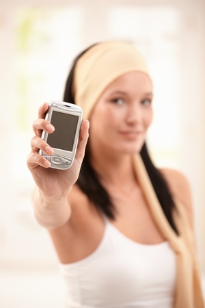 Young woman holding up mobile phone in hand in focus. Stock Photo - 8907508