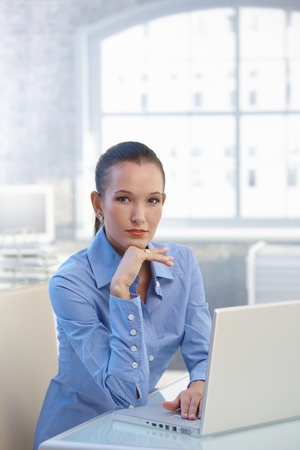 Portrait of young confident businesswoman sitting by computer looking at camera. photo