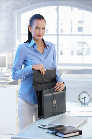 Portrait of young businesswoman opening briefcase in office, looking at camera. photo