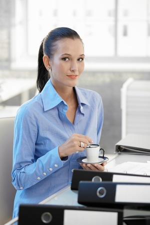 Smiling office worker girl having coffee, sitting at desk, looking at camera. photo