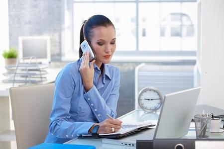 taking note: Imprenditrice concentrandosi su chiamata telefonica mobile, prendendo appunti. Archivio Fotografico