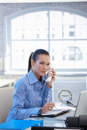Office worker girl taking landline call, writing notes, looking at camera, smiling. photo