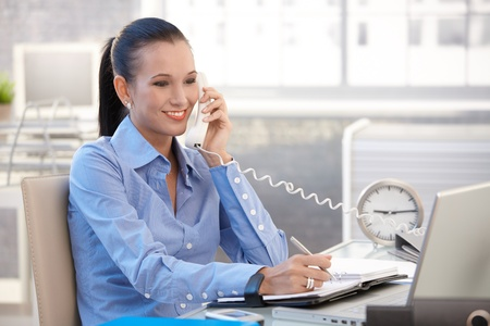 Happy office worker girl on landline phone call, smiling, listening to conversation. photo