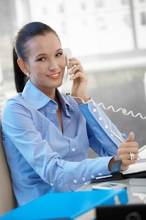 Happy businesswoman speaking on landline phone, smiling at camera. photo