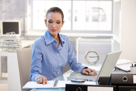 Businesswoman concentrating on work, looking at document, sitting at desk with laptop computer. photo