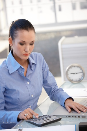 Office worker girl using calculator, busy with financial task at desk. photo