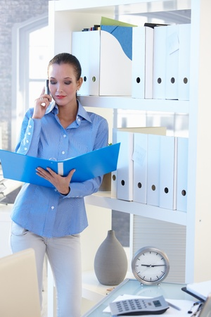 Businesswoman on mobile phone call checking documents in folder, standing at shelf. photo