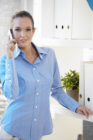 Portrait of pretty office worker on phone call, looking at camera, smiling. photo