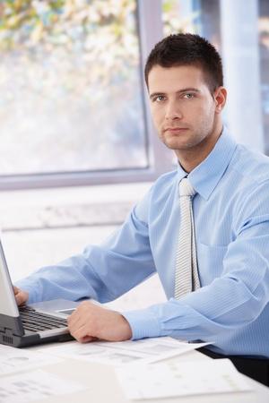 trabajador oficina: Apuesto joven empresario sentado en la Oficina brillante, trabajo en equipo port�til.