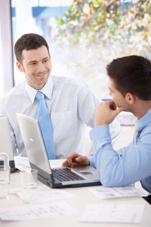 chat room: Young businessmen talking at meeting table, working together.