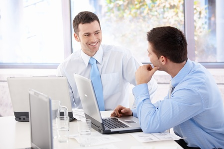 Handsome young businessmen chatting in meeting room, smiling. photo