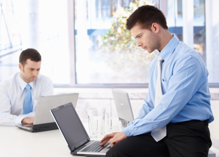 team from behind: Young businessmen working on laptop in bright office.