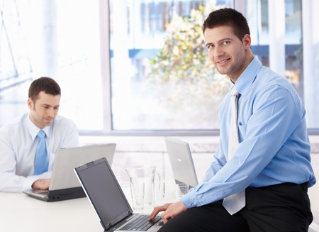 team from behind: Young businessman sitting on top of desk, working on laptop, smiling. Stock Photo