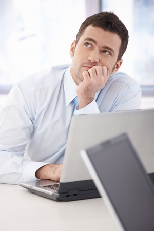 daydreaming: Handsome young businessman daydreaming at desk in office.