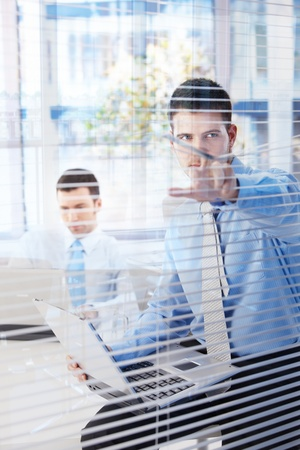 Young businessman working in office, peeping through blind. photo