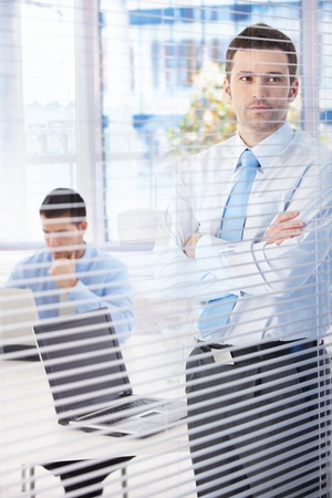 Young businessman standing in bright office, looking through blind, thinking. photo