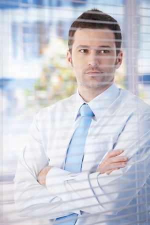 Portrait of young businessman standing in office, looking through blind thinking. photo