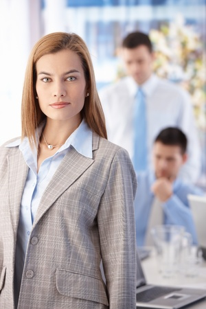 Attractive young businesswoman standing in bright office, colleagues working in background. photo