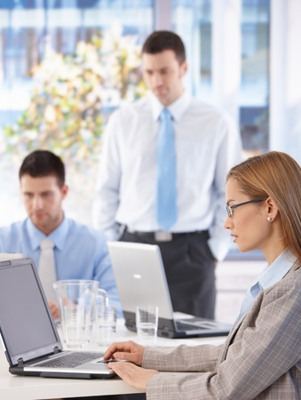 office work: Young businesswoman and team working in bright office.