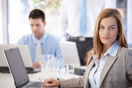 american staff: Beautiful young businesswoman sitting at desk in bright office, using laptop.