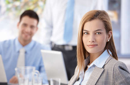 Portrait of attractive confident businesswoman working in busy office, colleagues behind. photo