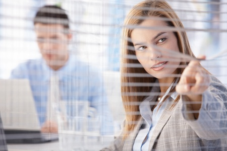 Young attractive businesswoman peeping through blind from bright meeting room. photo