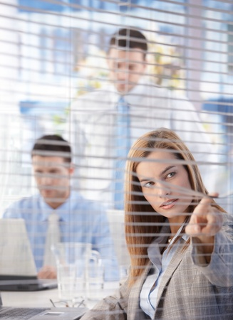 Attractive young businesswoman looking through blind in bright office. photo
