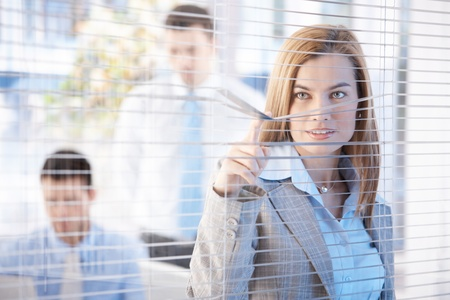 beautiful nosy businesswoman peeping through blind in bright office smiling stock photo 8951313 beautiful bright office