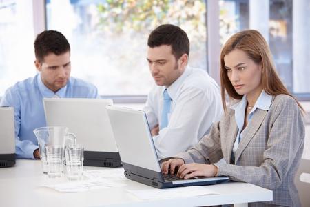 trabajador oficina: J�venes empresarios trabajando en equipo port�til sentado en la sala de reuniones.