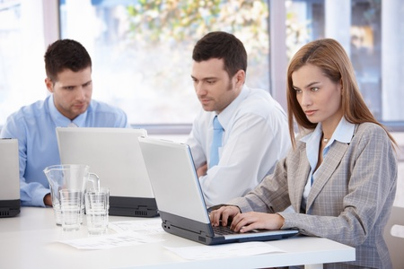 BUSY OFFICE: Young businesspeople working on laptop sitting in meeting room. Stock Photo