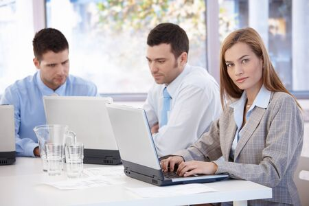 Attractive young businesswoman and colleagues working in meeting room. photo