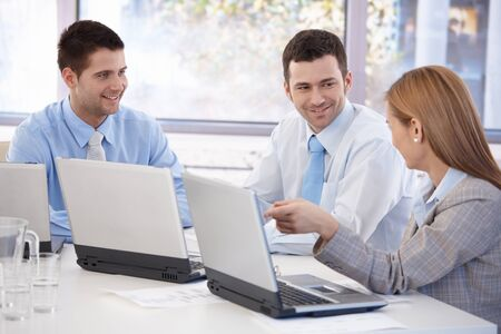 co worker: Happy team of young businesspeople working together in meeting room. Stock Photo